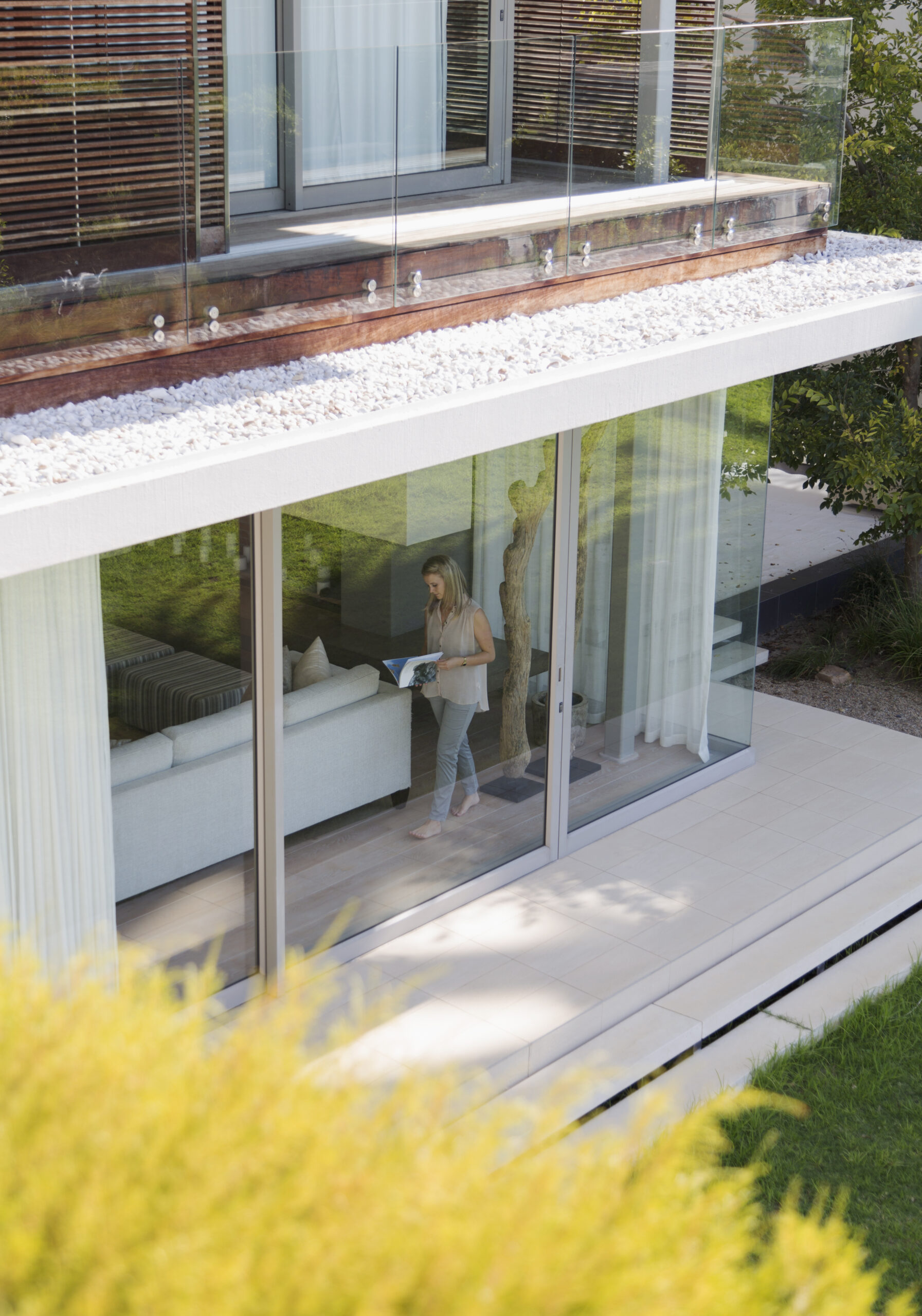 Woman reading book at window of luxury modern house